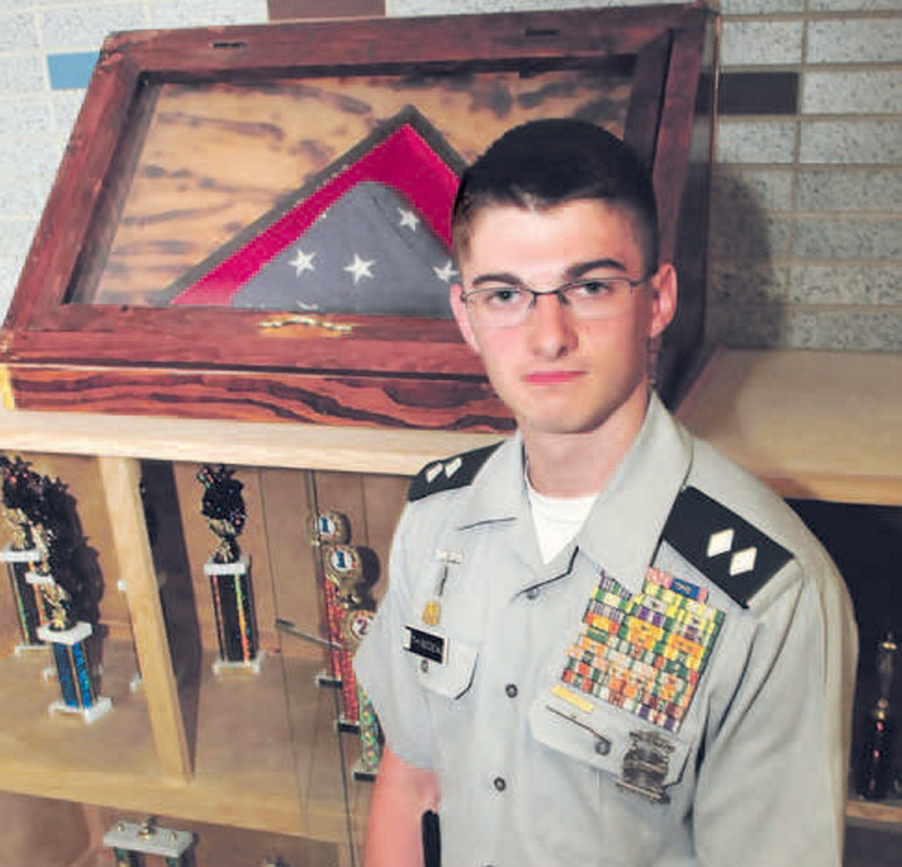 Staff photo by David Leaming RECOGNITION: Nokomis Regional High School student Felix Thibodeau who is also a Cadet Lt. Col. of the Nokomis JROTC Battalion, stands beside an organization trophy case at the school in Newport on Monday, June 2, 2014. Thibodeau is being recognized for his efforts to raise money and awareness for the Togus Veterans Association Homeless Veterans Department.