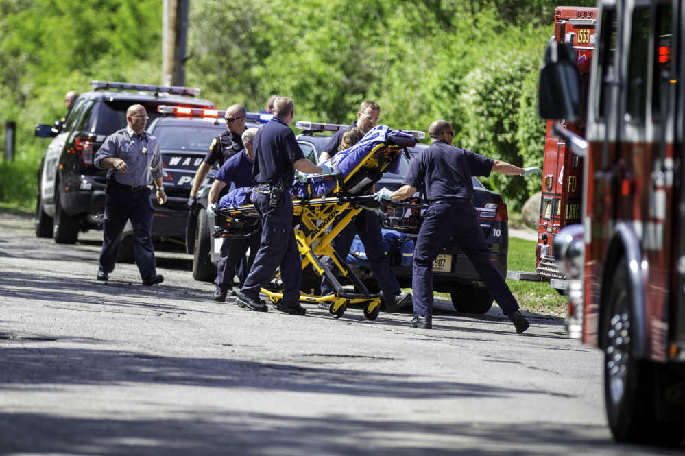 Rescue workers take a stabbing victim to an ambulance in Waukesha, Wis., on Saturday. Two 12-year-old girls are charged in the attack.