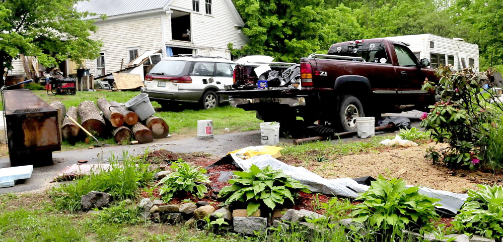 Staff photo by David Leaming CLUTTER: The front yard at the Wilton home of Duane Pollis is littered with disabled vehicles and household items beside a barn and a trailer.