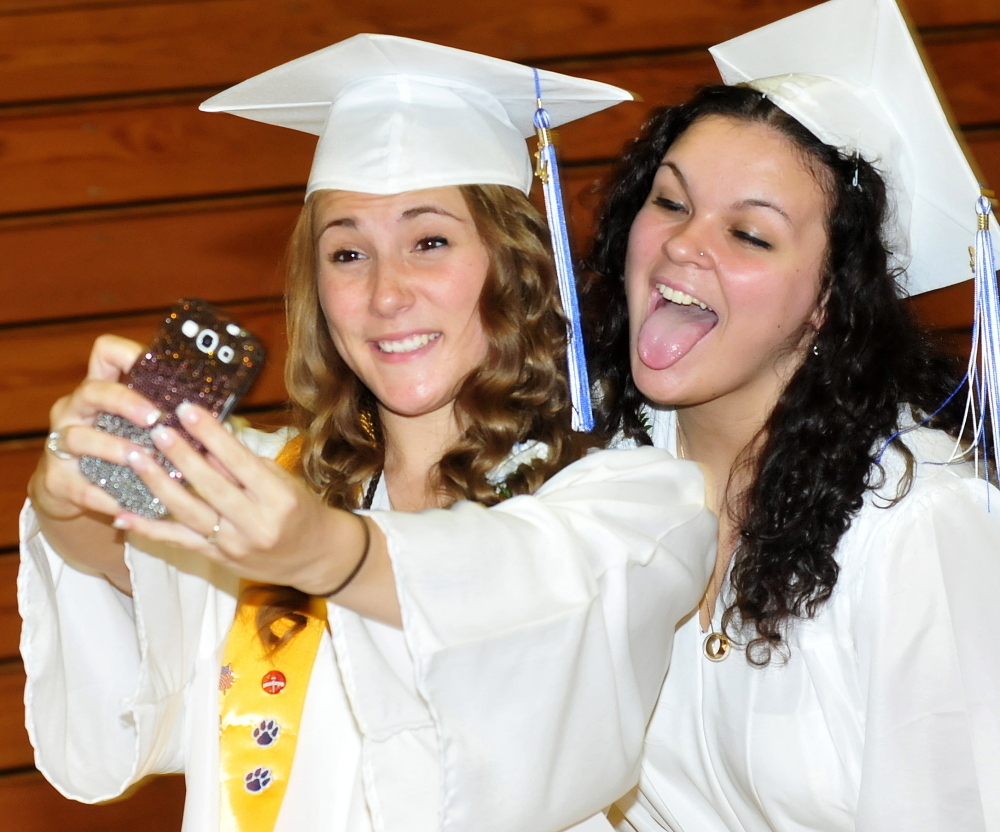 Staff photo by David Leaming SELFIE SELFIE: Lawrence High School students Aubrey Kressler, left, and Baylee Dugal pose for their own selfie portrait during commencement in Fairfield on Thursday.