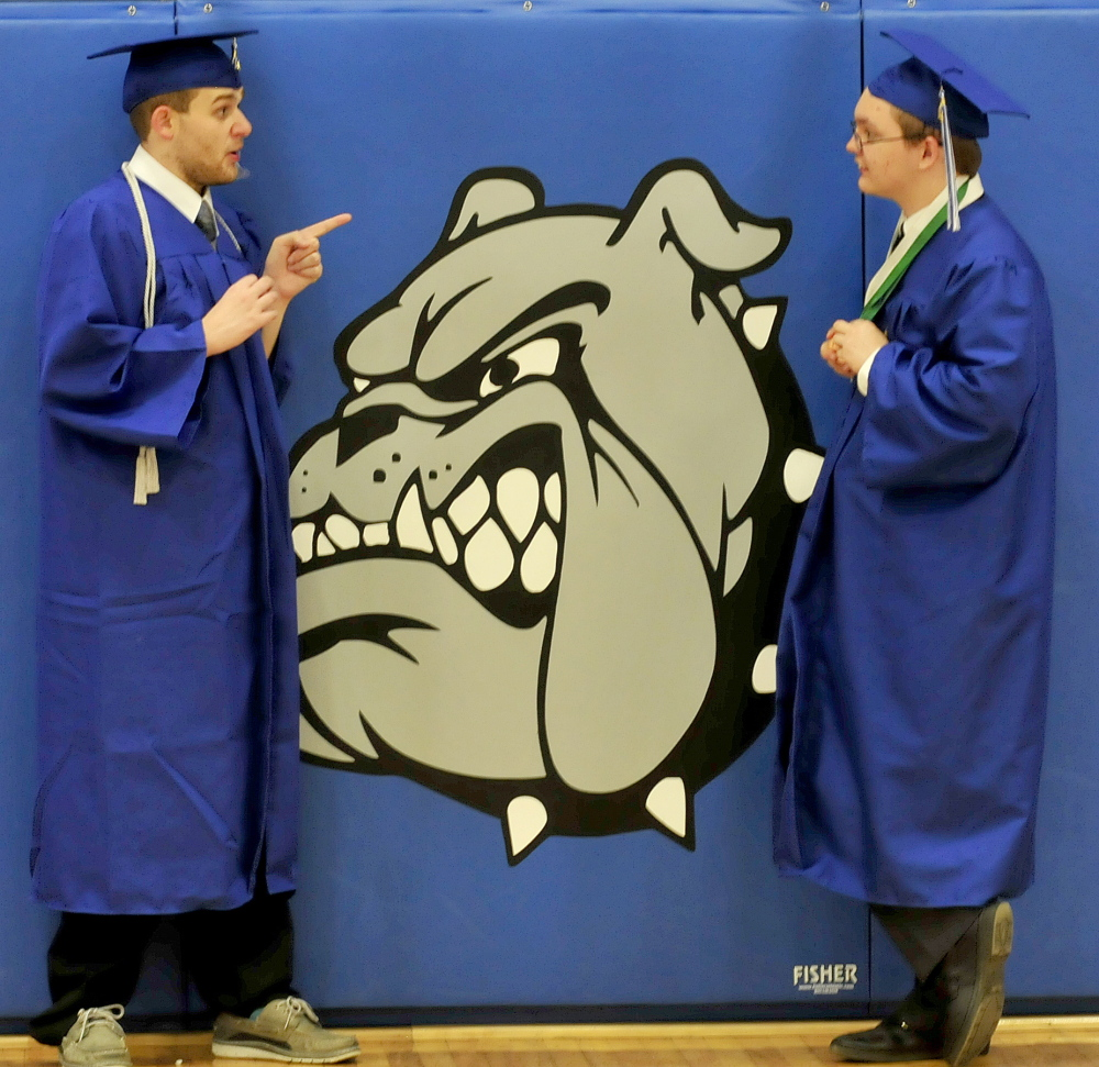 Staff photo by David Leaming DOG GONE FINISHED: Lawrence High School graduates have a last minute serious discussion beside the school mascot shortly before commencent in Fairfield on Thursday. Logan Rogers, left, and Brandon Dillon-Mulcahy share some thoughts.
