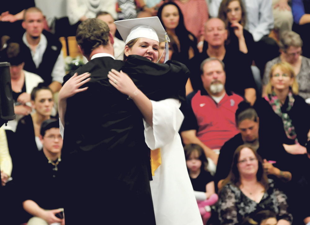 Staff photo by David Leaming THANKS: Lawrence High School Honors Speaker Josie Champagne is hugged on stage by teacher Tyler Duran during commencement in Fairfield on Thursday.