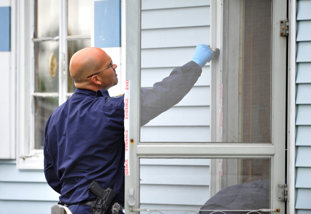 Staff photo by Michael G. Seamans Evidence: An investigator with the Maine State Police Major Crimes Unit dusts for fingerprints at the residence of Aurele Fecteau, 92, who was found dead in his home on Brooklyn Street in Waterville on Friday, May 23.