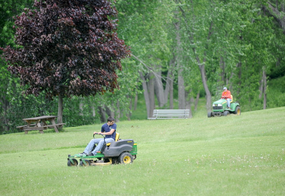 Staff photo by Michael G. Seamans Getting Ready: Winslow Parks and Recreation workers mow the grass at Fort Halifax Park in Winslow on Friday. Fort Halifax will host the Winslow Family 4th of July Celebration from July 2-4.