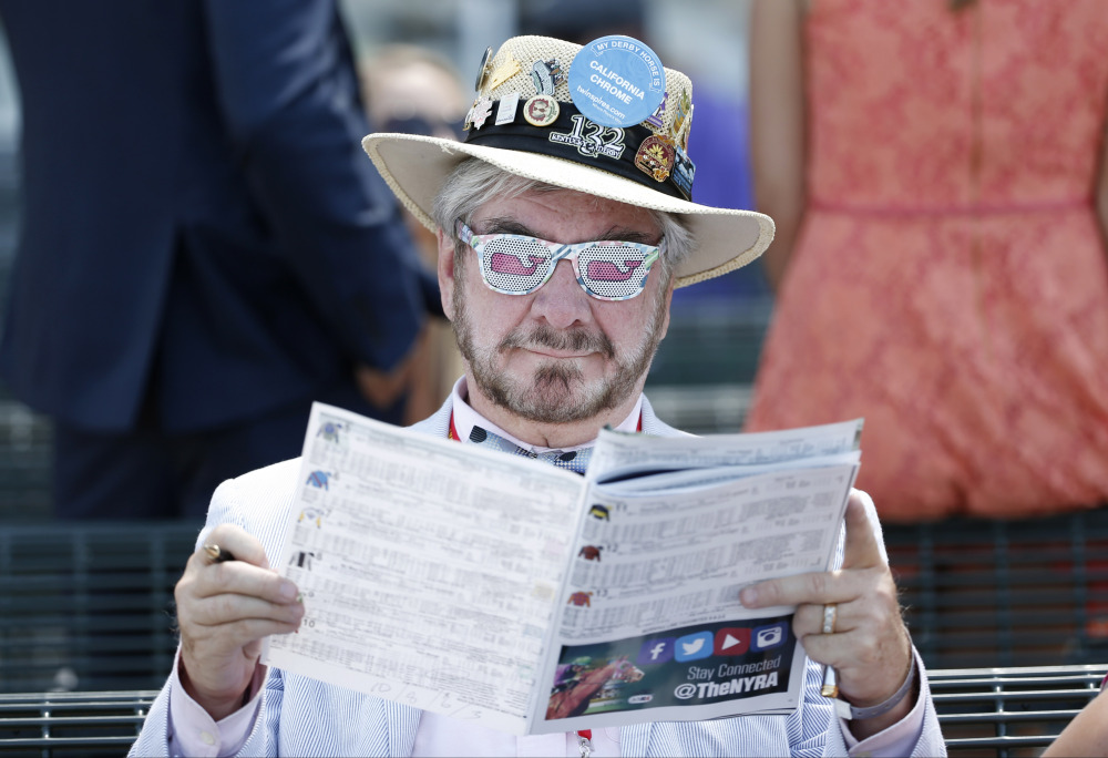 The Associated Press/Kathy Willens Charles Clarke III reads a program at Belmont Park before the Belmont Stakes horse race, Saturday, June 7, 2014, in Elmont, N.Y.