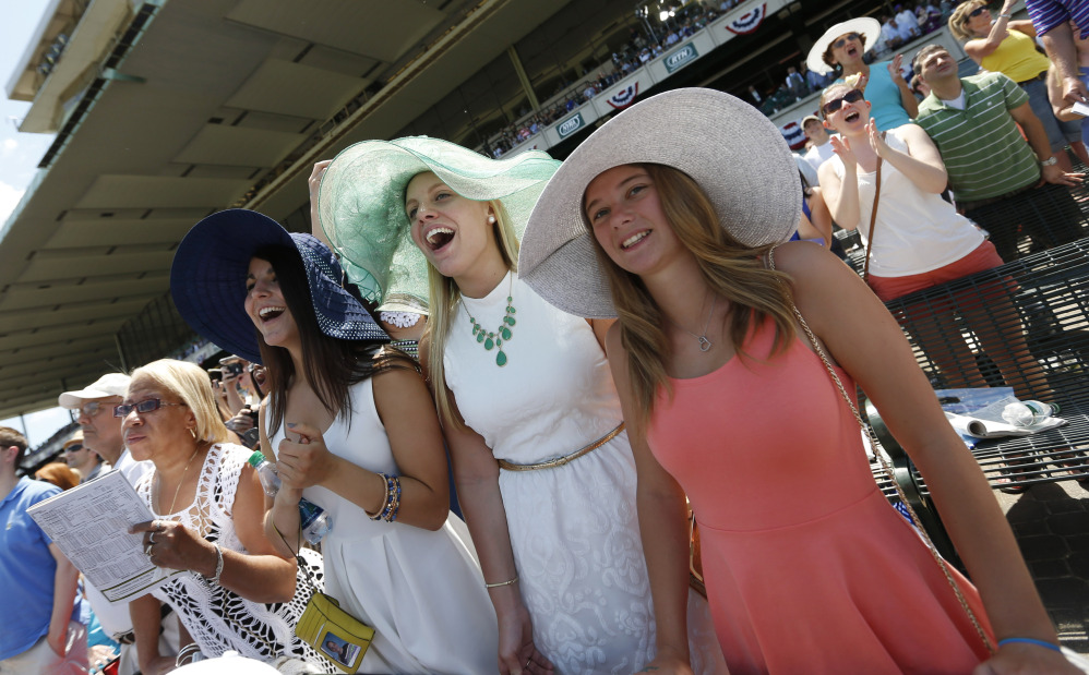The Associated Press/Jason DeCrow Jen Hylkema, left, Rosalie Chamiel, center, and Annie Westlake cheer at Belmont Park before the Belmont Stakes horse race, Saturday, June 7, 2014, in Elmont, N.Y.