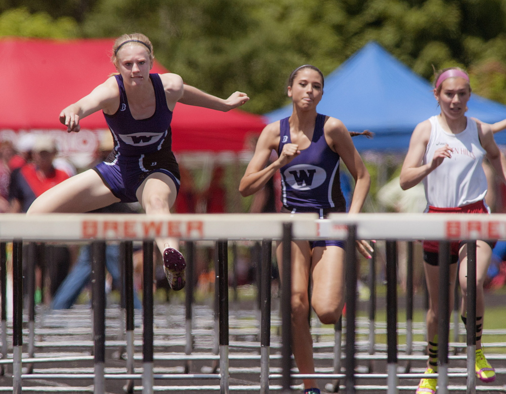 Staff photo by Michael York Winners: Sarah Shoulta, left, and teammate Kellie Bolduc, middle, from Waterville High School finish first and second respectively in the Girls 100m hurdles final on Saturday in Brewer.