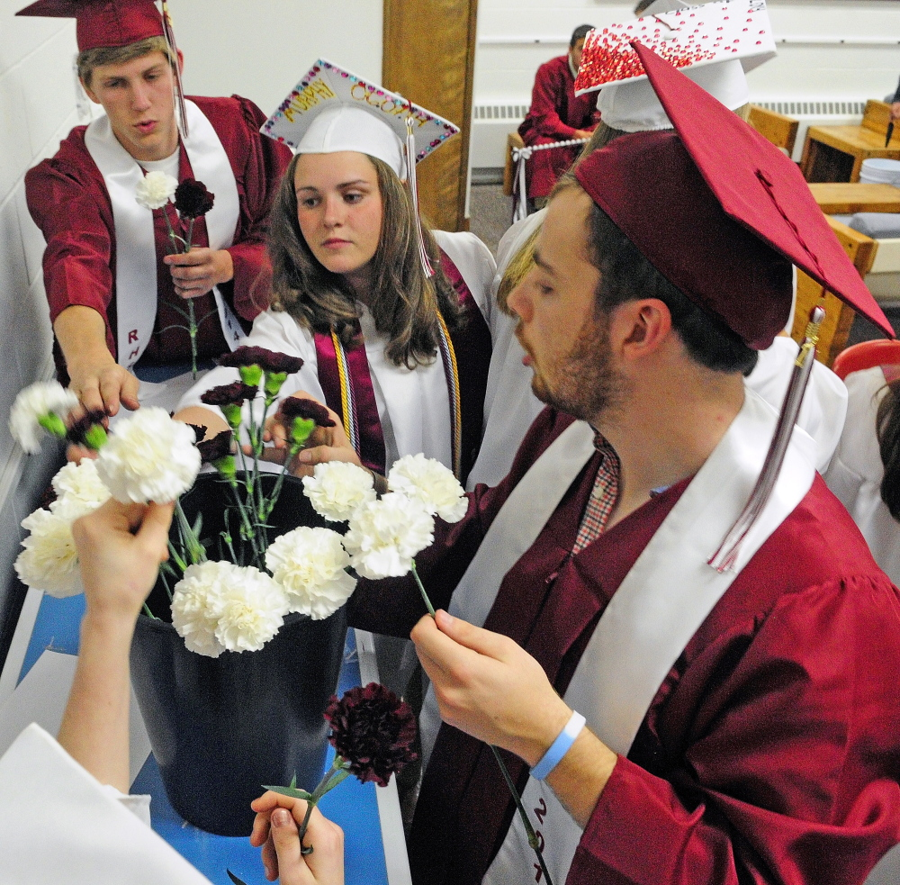 Staff photo by Joe Phelan Final token: Before their graduation ceremony, seniors take a carnation Saturday at Richmond High School to give to a special person in their life.