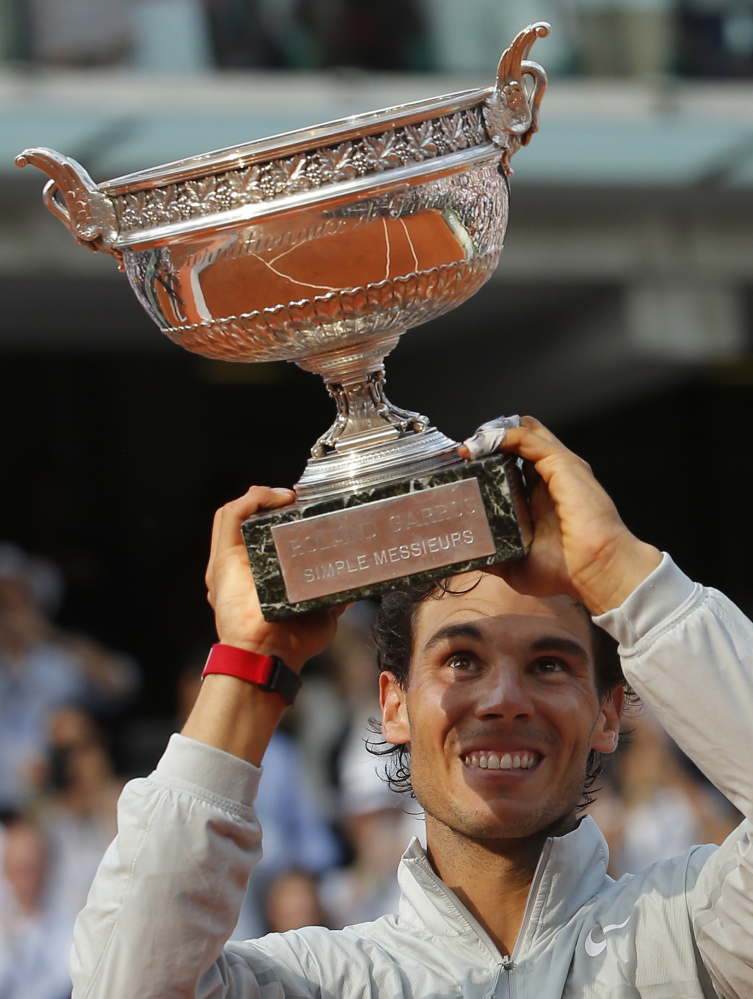The Associated Press Rafael Nadal lifts up his cup after defeating Novak Djokovic in their final match of the French Open Sunday in Paris.