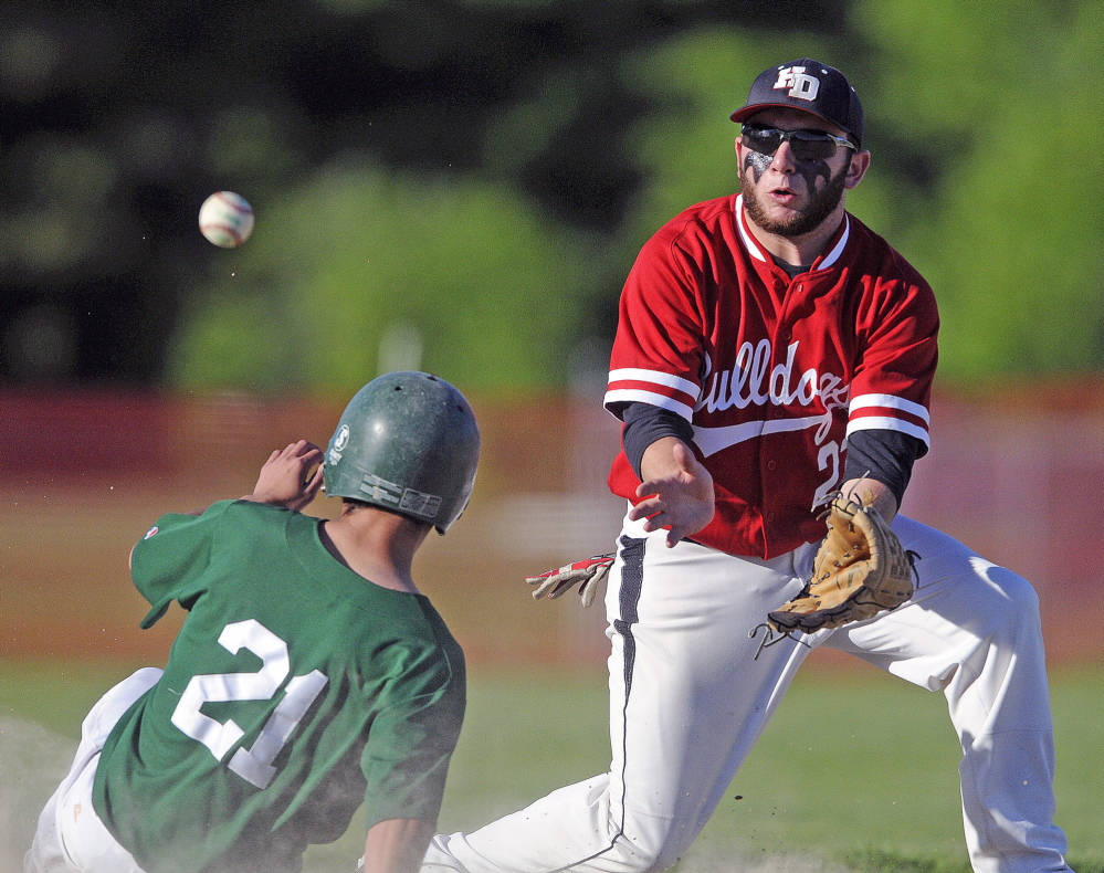 Staff photo by Andy Molloy Pitcher: Hall-Dale High School's Alex McPherson can collect a throw to second in time to pick off Winthrop High School's Drew Stratton Tuesday during a baseball match up in Farmingdale.