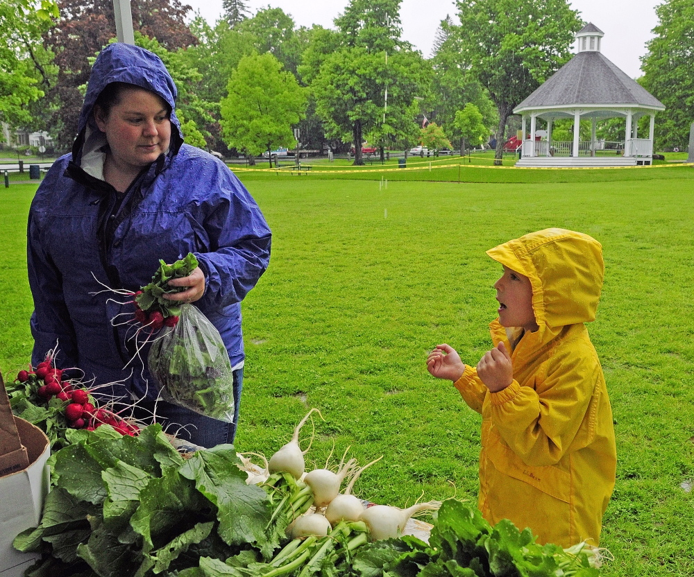 Staff photo by Joe Phelan FRESH AND NEW: Christine Leavitt, left, and Rylee Lefebvre buy vegetables in front of the newly built gazebo on a rainy day last week during the twice weekly market on the Gardiner Common. A ribbon cutting and dedication ceremony at the gazebo will be held from 11 a.m. to 1 p.m. Saturday.