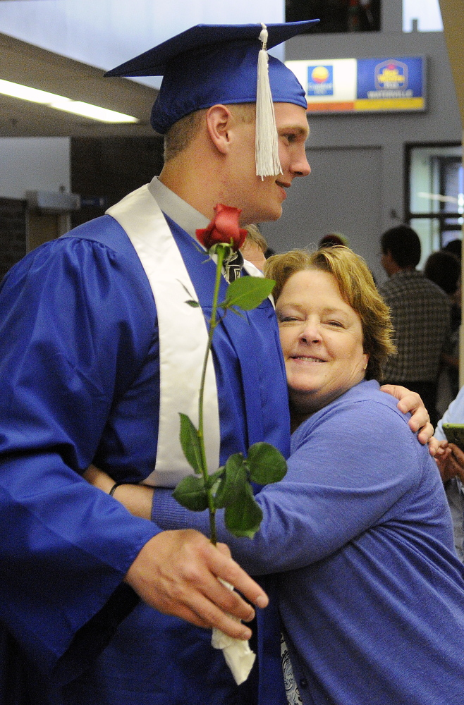 Staff photo by Andy Molloy ALL DONE: Kim Tessari hugs her nephew, Luke Washburn, Monday during graduation ceremonies in Augusta for Oak Hill High School.