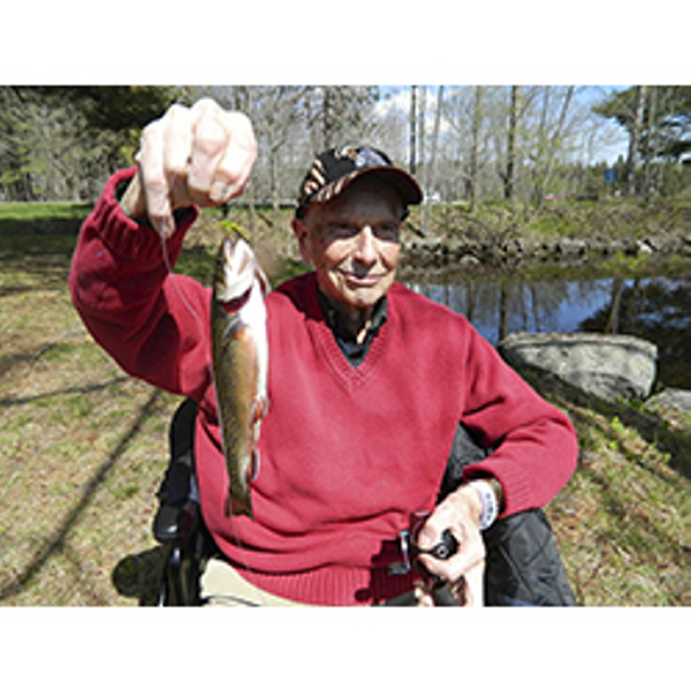 Photo by George Smith   STILL FISHING: Ezra Smith proudly holds a trout he caught recently from a small pond on the campus of the Veterans Affairs facility at Togus.