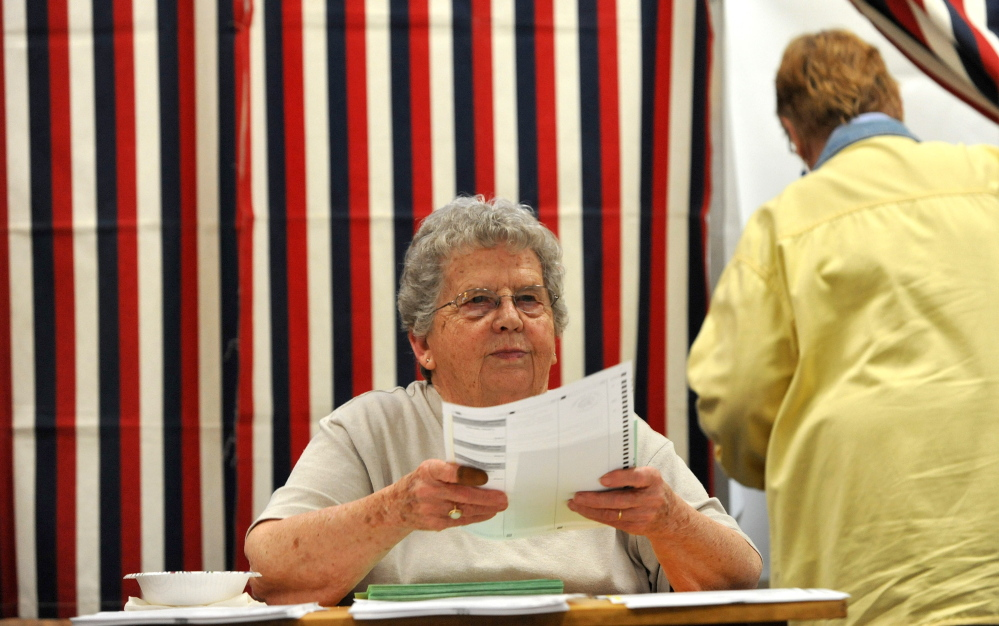 Staff photo by Michael G. Seamans   Loraine Arsenault, election clerk, hands out ballots at the Skowhegan Town Office during primary voting on Tuesday, June 9, 2014.