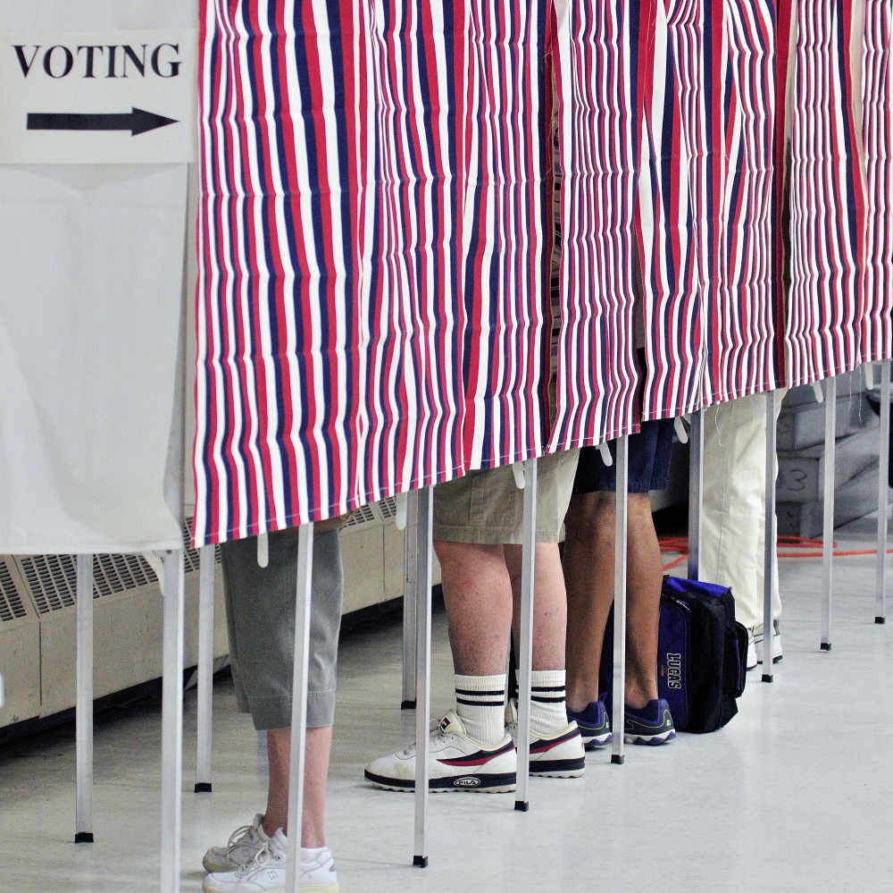 Staff photo by Joe Phelan Augusta Voting: Four voters cast ballots in voting booths Tuesday in Ward 1 at Augusta Armory.