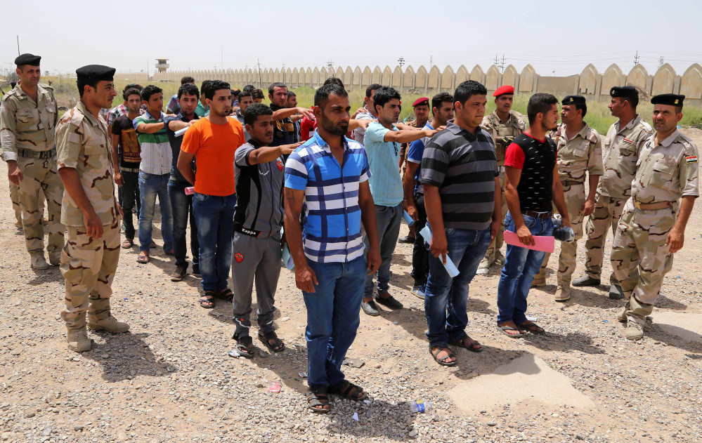 Iraqi men line up outside of the main army recruiting center to volunteer for military service in Baghdad on Thursday after authorities urged Iraqis to help battle insurgents.