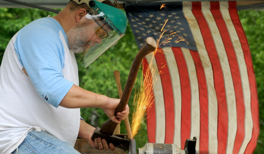 PATRIOTIC DISPLAY: Vern Burke, of Skowhegan, flies his American flag as sharpens an ax in his SwiftWater Edge Tool Works tent at his West Front Street residence on Friday. Saturday is Flag Day, commemorating the formal adoption of the stars and stripes as the official flag of the United States in 1777.