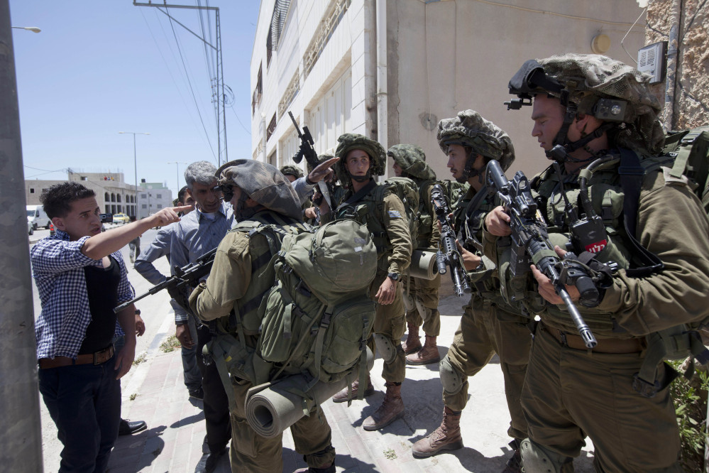 A Palestinian youth argues with Israeli soldiers as he tries to enter his home during a military operation to search for three missing teenagers outside the West Bank city of Hebron on Sunday.