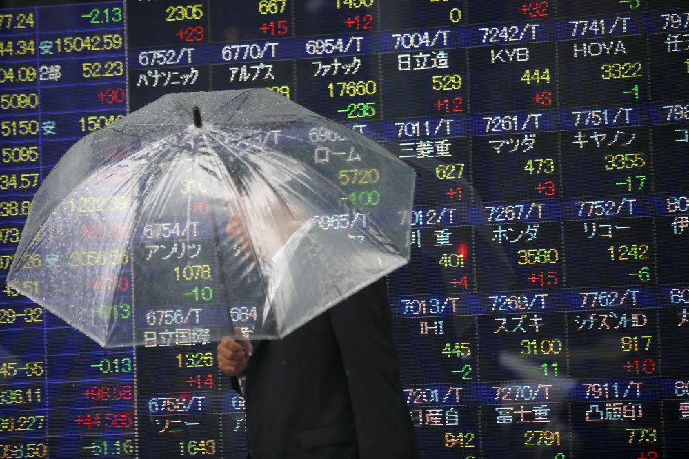 In this file photo, a man holding an umbrella walks past an electronic stock indicator of a securities firm, in Tokyo. The Treasury Department releases foreign holdings data for April on Monday.