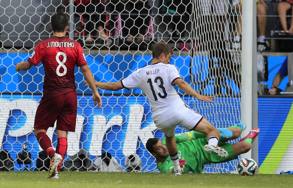 Germany's Thomas Mueller, center, scores his sides third goal during the group G World Cup soccer match between Germany and Portugal at the Arena Fonte Nova in Salvador, Brazil, Monday, June 16, 2014.