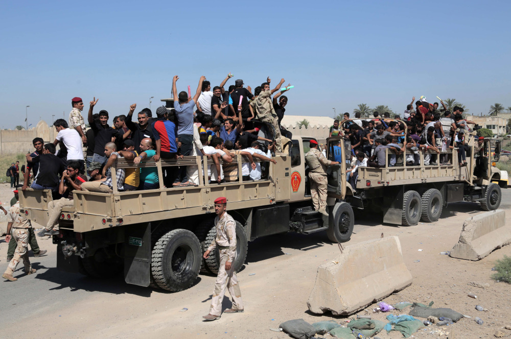 Iraqi men fill military trucks to join the Iraqi army at the main recruiting center in Baghdad, Iraq, Tuesday, after authorities issued a call to arms.