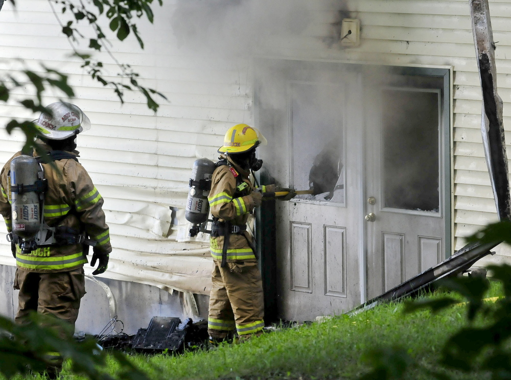 House Fire: Firefighters break glass in doors to vent fire that did extensive damage to a cottage on North Pond in Smithfield on Wednesday.