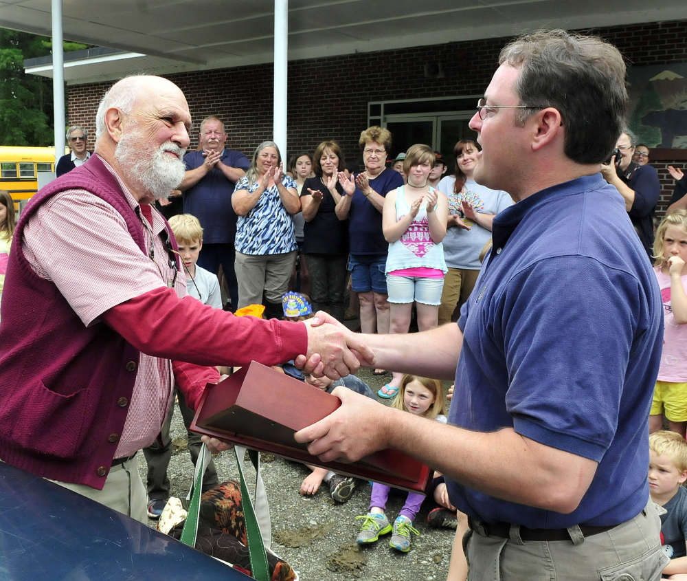 THANKS: Cornville Regional Charter School Principal William Crumley, left, is presented a folded American flag by Executive Director Justin Belanger during a ceremony marking Crumley leaving the school on Wednesday.