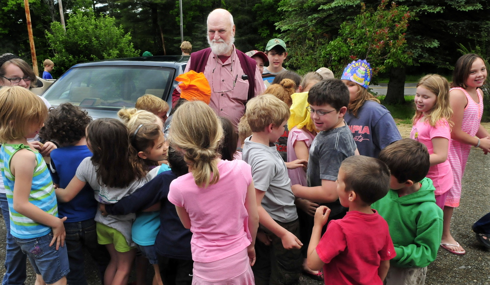 APPRECIATION: William Crumley is surrounded by hugging students at the Cornville Regional Charter School during a ceremony marking his leaving as school principal on Wednesday. An American flag was raised and lowered and presented to Crumley and a time capsule was sealed during the event.