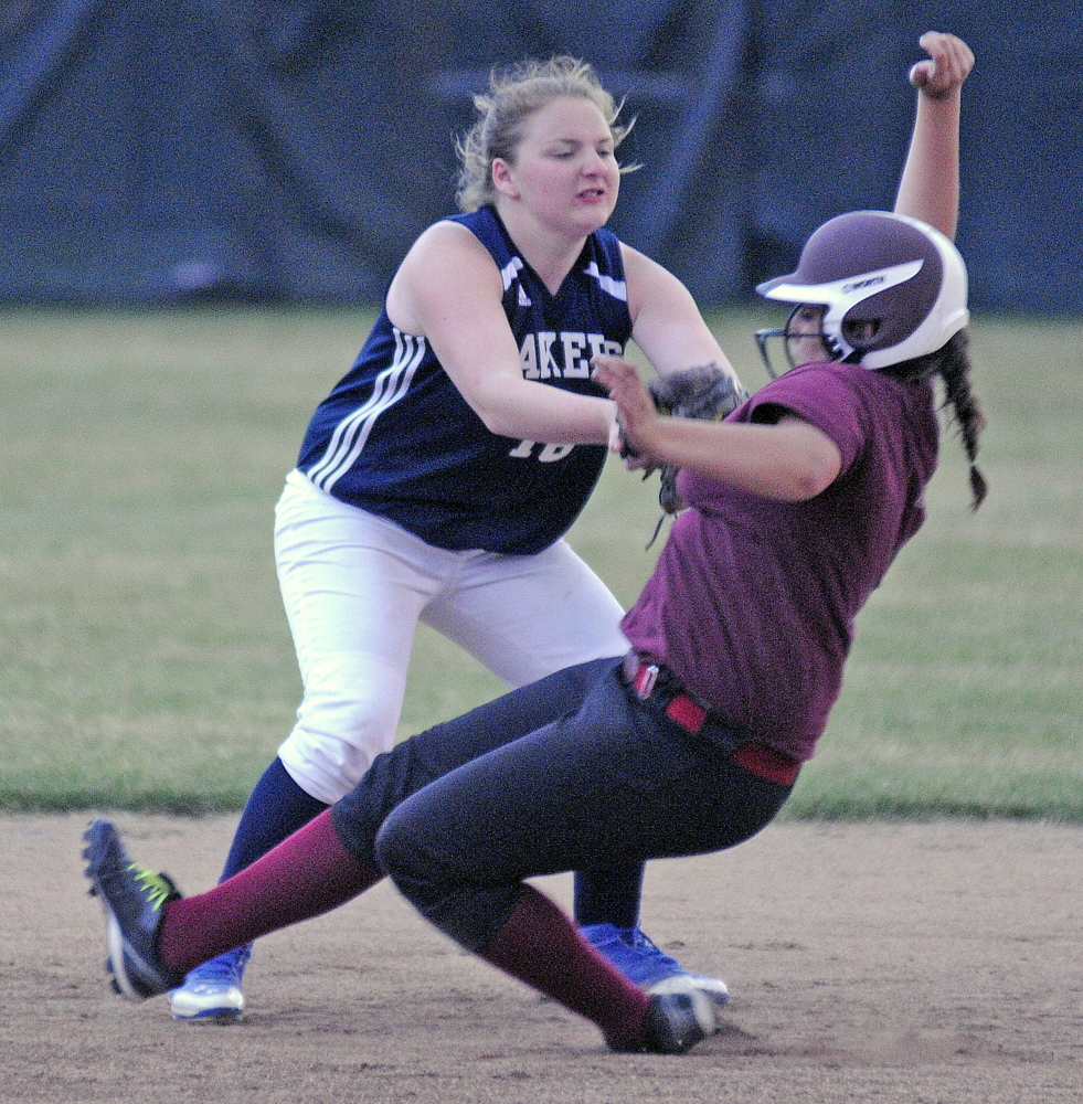 Richmond High School's Emily Douin gets snagged by Greenville High School's Danielle Mills during the Western D softball final on Wednesday June 18, 2014 in Standish.
