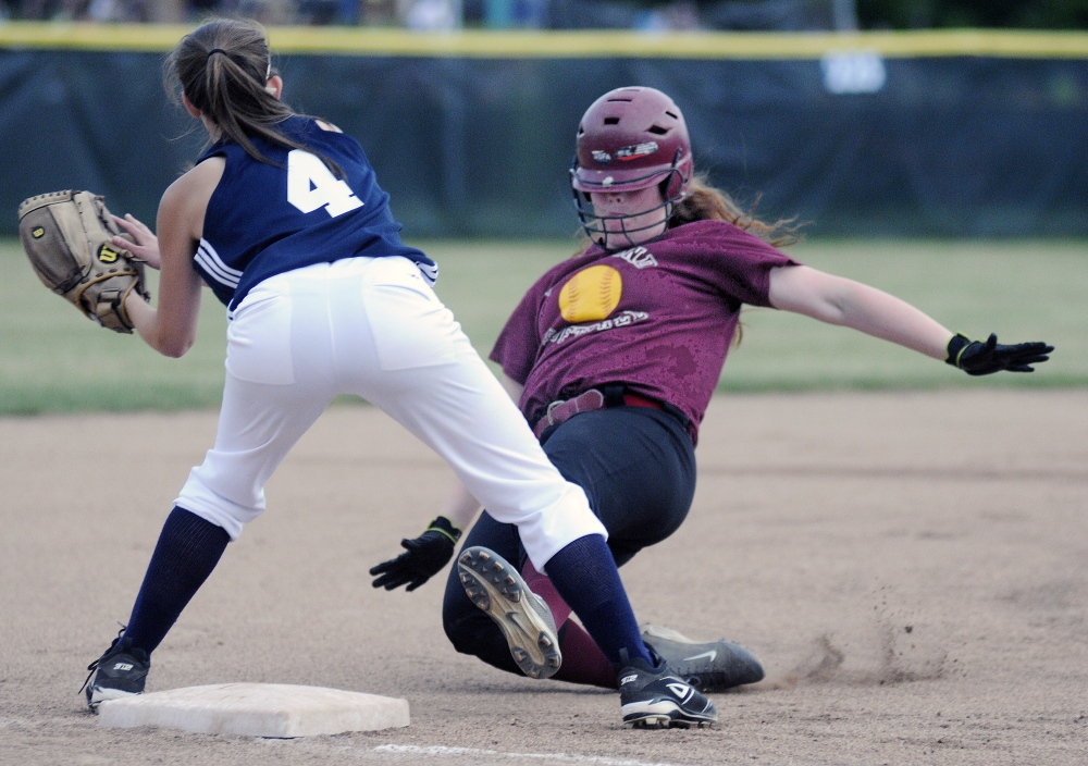 Richmond High School's Kalah Patterson slides under the tag of Greenville High School's Grace Bilodeau during the Western D softball final on Wednesday June 18, 2014 in Standish.