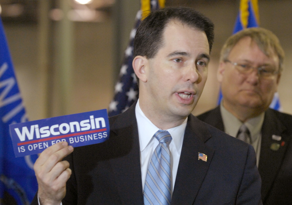 Wisconsin Gov. Scott Walker holds a bumper sticker with his signature campaign promise for the state in this 2011 photo. Walker rose to fame shortly after taking office in 2011, passing a bill that effectively ended collective bargaining for most public workers.
