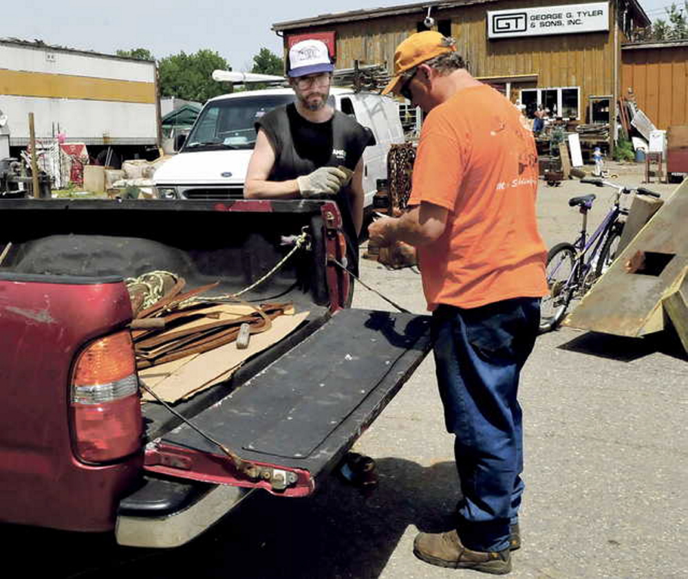 LEGAL BATTLE LOOMS: Robert Dale, left, owner of Maine 201 Antiques in Fairfield, completes a sale with customer Robert Plourde earlier this month. Dale failed to meet Sunday's deadline for cleaning the property.