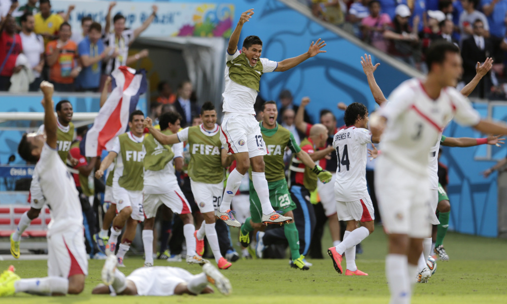 Costa Rican players come off their bench to celebrate their 1-0 victory over Italy during the group D World Cup soccer match between Italy and Costa Rica at the Arena Pernambuco in Recife, Brazil, on Friday.