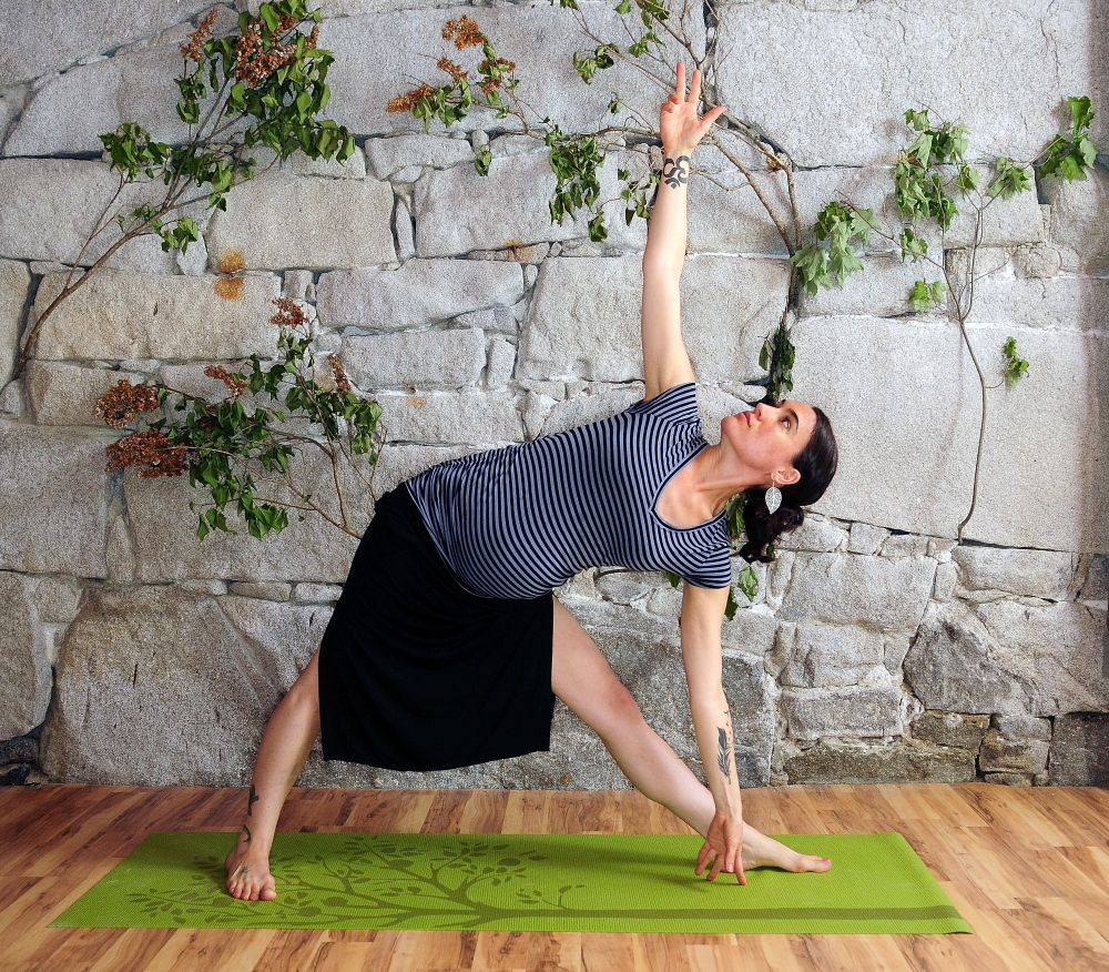 Suzanne Imbruno Cobb, who says yoga helped ease her Lyme disease, demonstrates a triangle pose at Panacea Yoga Studios at 101 Second St. in Hallowell.