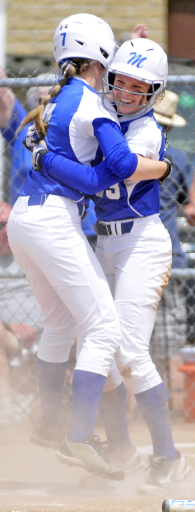 Madison's Kirstin Wood hugs teammate Madeline Wood after crossing home plate to score the Bulldog's only run during the class C softball state championship on Saturday in Standish. The Bulldogs beat Calais 1-0 for the title.