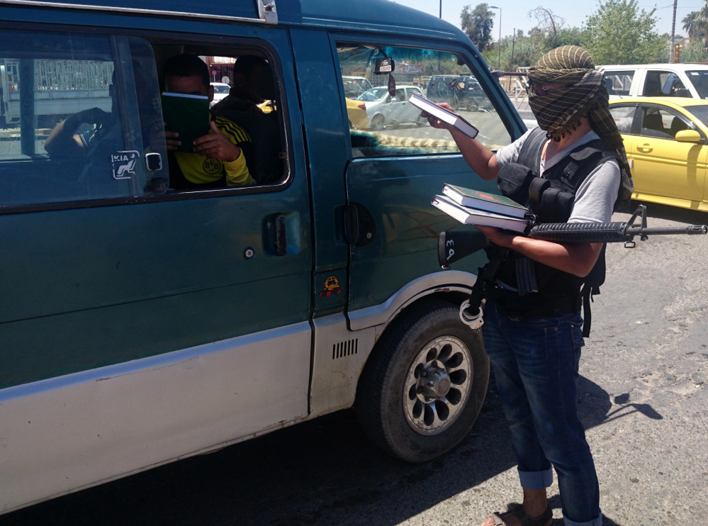 A fighter with the al-Qaida-inspired Islamic State of Iraq and the Levant (ISIL) distributes a copy of the Quran, Islam's holy book, to a driver in central northern city of Mosul, 225 miles northwest of Baghdad.