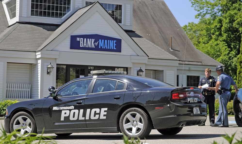 Robbery: Police confer Monday outside of the Bank of Maine branch in Hallowell, where a man reportedly in his 70s robbed the bank and threatened to use a grenade.