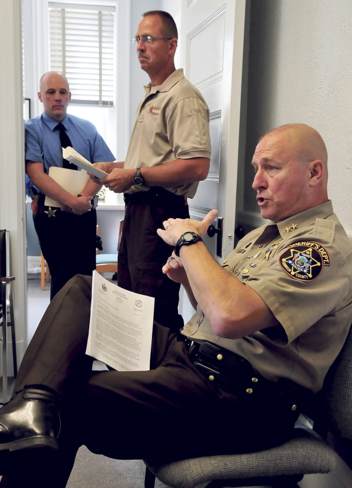 Franklin County Sheriff Scott Nichols, seated, explains how the department will come up with an additional $100,000 for the state Board of Corrections during a meeting with county commissioners in Farmington Tuesday. Waiting to speak at left is Chief Deputy Steve Lowell, left, and jail administrator Doug Blauvelt.