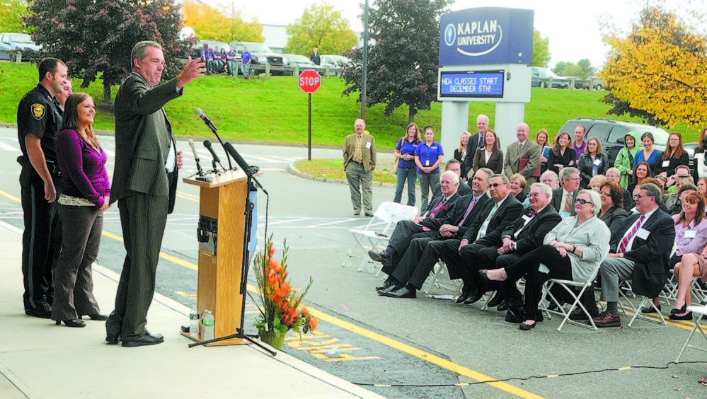 Kaplan University students Augusta Police Officer Matthew Estes, left, and his wife, Jennifer Estes, are introduced by Christopher Quinn, president of Kaplan University Maine, during an opening ceremony for the company's new Augusta center in October 2012.