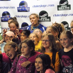 Julia Clukey makes faces while posing with campers after she announced that she'll compete for at least one more year on the World Cup luge circuit after a press conference Tuesday.
