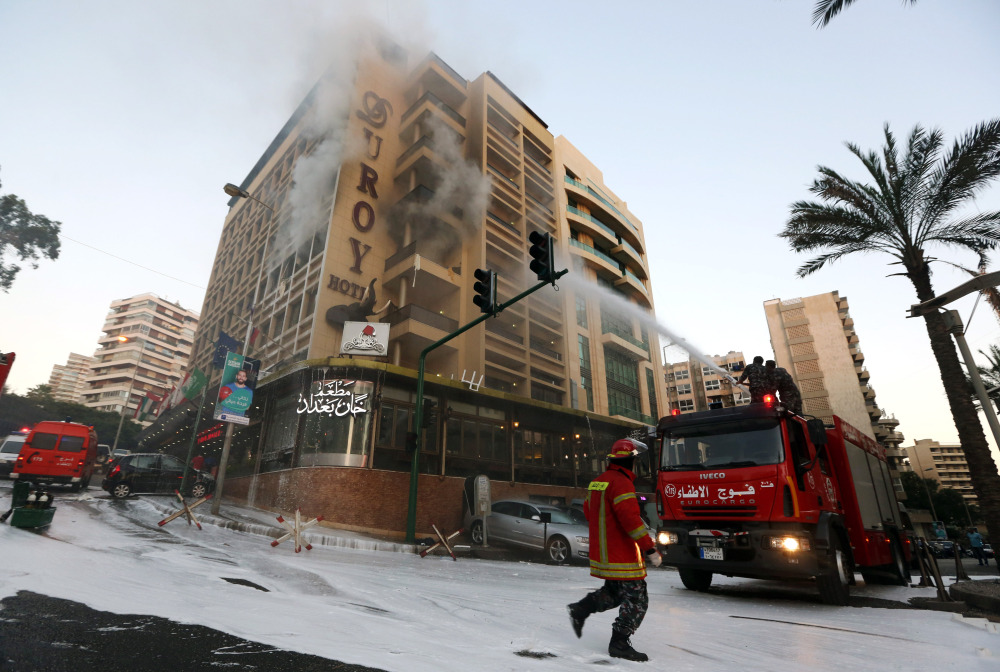 Firefighters work to extinguish a fire after a suicide bomber blew himself up in his room at a Beirut hotel in Lebanon on Wednesday.