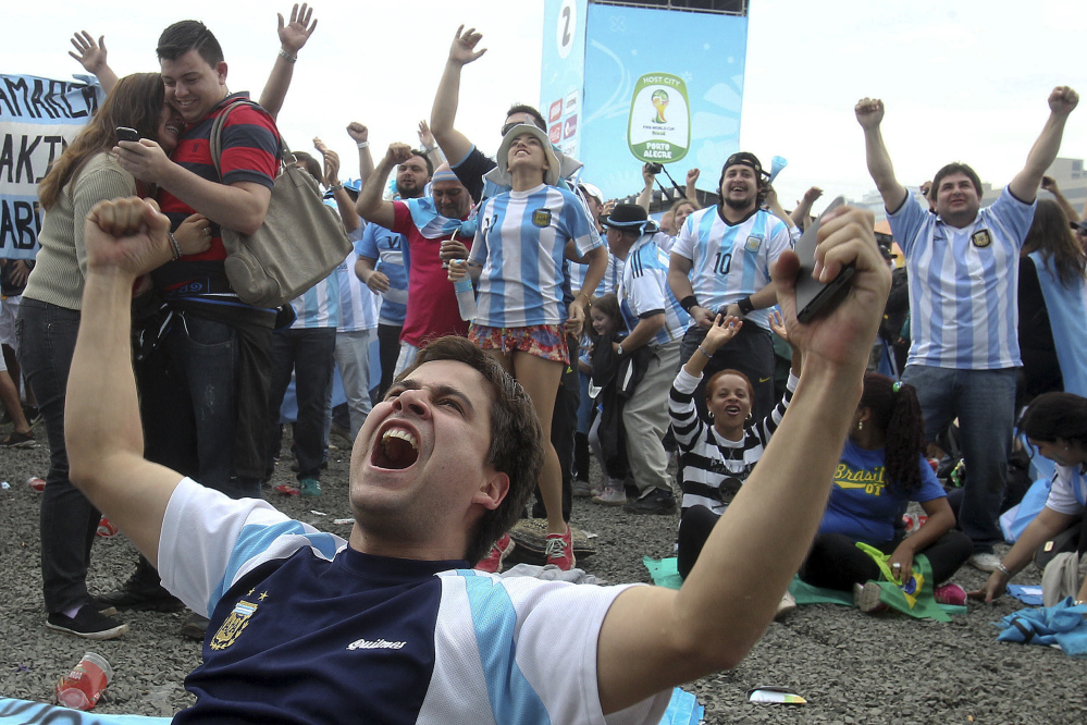 Argentina soccer fans celebrate after watching their side score a goal, via a live telecast of the World Cup group F match between Argentina and Nigeria, inside the FIFA Fan Fest area, in Porto Alegre, Brazil, Wednesday, June 25, 2014. (AP Photo/Nabor Goulart)