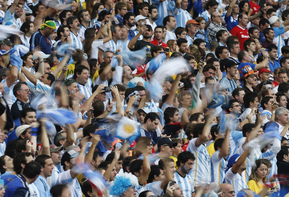 Argentine fans wave national flags Argentina's Lionel Messi is replaced after scoring two goals for his side during the group F World Cup soccer match against Nigeria at the Estadio Beira-Rio in Porto Alegre, Brazil, Wednesday, June 25, 2014. (AP Photo/Jon Super)