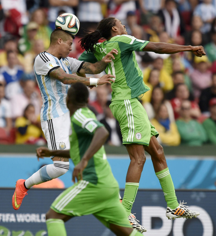 Argentina's Marcos Rojo, left, goes up to head the ball over Nigeria's Michael Uchebo during a World Cup soccer match in Porto Alegre, Brazil, on Wednesday.