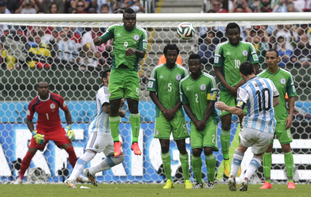 Argentina's Lionel Messi, second right, scores his side's second goal on a free kick during the group F World Cup soccer match between Nigeria and Argentina at the Estadio Beira-Rio in Porto Alegre, Brazil, Wednesday, June 25, 2014. (AP Photo/Fernando Vergara)