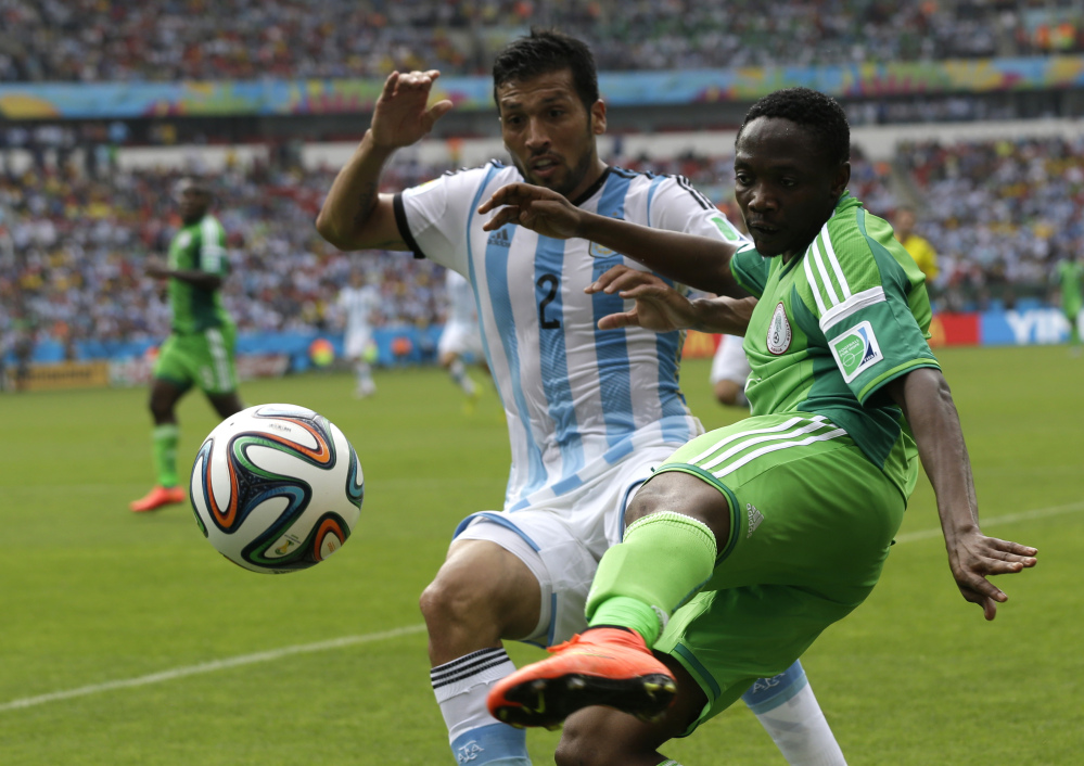 Nigeria's Ahmed Musa, right, and Argentina's Ezequiel Garay challenge for the ball during the group F World Cup soccer match between Nigeria and Argentina at the Estadio Beira-Rio in Porto Alegre, Brazil, Wednesday, June 25, 2014. (AP Photo/Fernando Vergara)