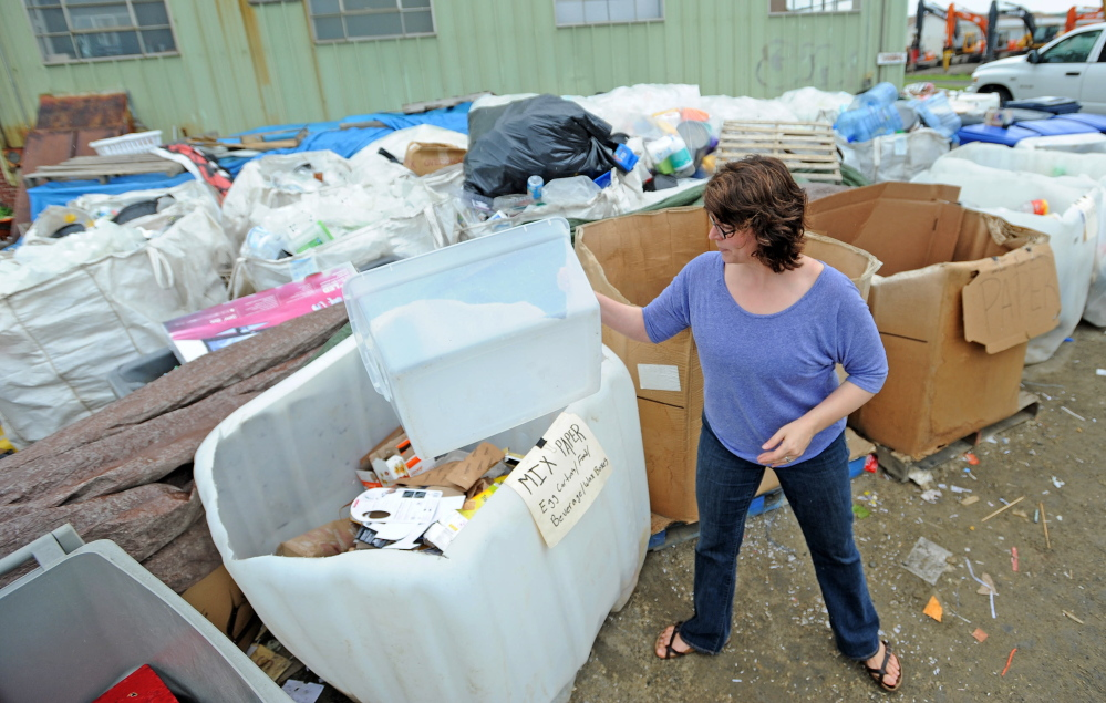 Amy Bongard, of Fairfield, manually sorts her recyclable materials into assigned bins at the Waterville Recycling Center at Shredding On Sight on Armory Road in Waterville on Wednesday, June 25, 2014.