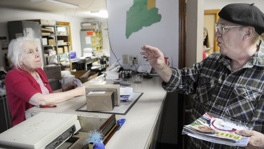Mel Mounts confers with Postmaster Sheila Sanford Wednesday at the post office in North Monmouth. Mounts said he's not concerned about reduced hours because he's retired, but understands it could be a problem for those who work.