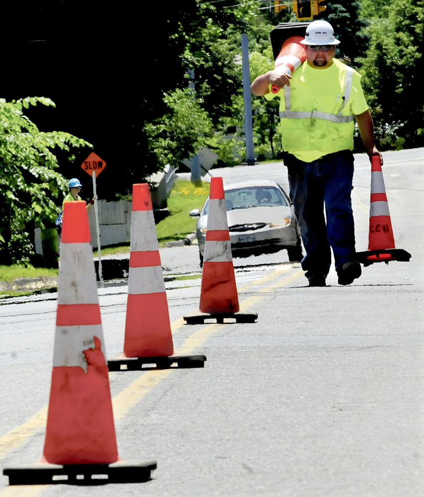Mark Franzose picks up some of the dozens of traffic cones that were used by workers installing a natural gas pipeline on Cool Street in Waterville on Monday.