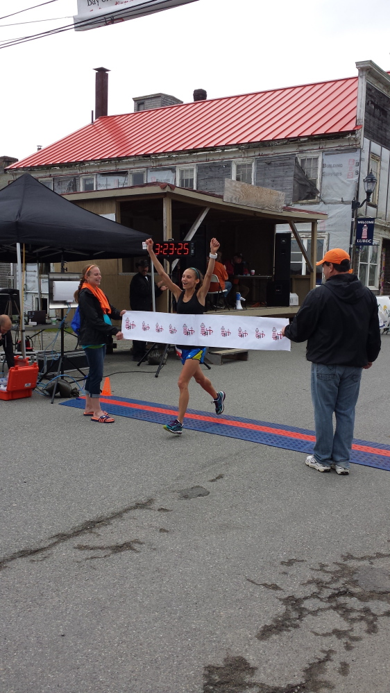 Courtesy photo   Lydia Kouletsis, 22, of Oakland, crosses the finish line at the Bay of Funday International Marathin in Lubec last month. Kouletsis was the top female finisher with a time of 3 hours, 23 minutes and 24 seconds